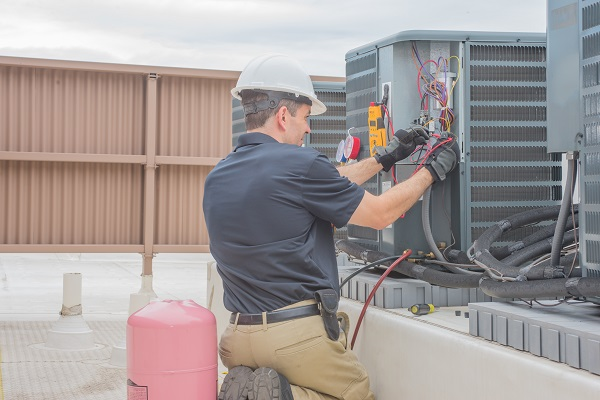 Technician checking for power on a rooftop condensing unit.
